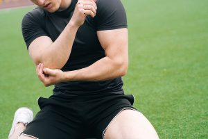 Male athlete sitting on a green field and gripping his painful elbow