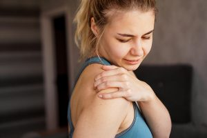 Blonde women rubbing her painful shoulder after exercising at home