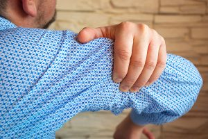 Man in blue shirt feeling sharp pain in his biceps muscle