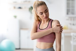 Woman gripping her painful shoulder after working out in a gym